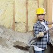 Stock Photo: Female contractor digging sand at construction site