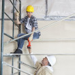 Male worker giving drill to woman on scaffold at construction site — Stock Photo #21891063