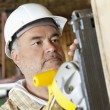 Serious male construction worker cutting wood with a power saw — Stock Photo #21891195