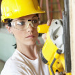 Serious female construction worker cutting wood with a power saw — Stock Photo #21891205