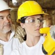 Female worker cutting wood with a power saw while male worker standing behind — Stock Photo