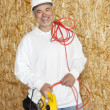 Portrait of a happy male construction worker holding a power saw and a red electric wire — Stock Photo #21891229