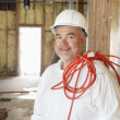 Portrait of a construction worker with a red electric wire — Stock Photo