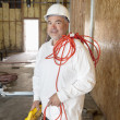 Portrait of a smiling male construction worker holding a power saw and a red electric wire — Stock Photo #21891241