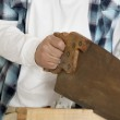 Midsection of male construction worker cutting wood with handsaw — Stock Photo