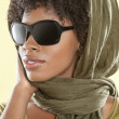 African American woman wearing sunglasses with stole over her head - Stock Photo