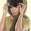 Portrait of an African American woman holding sunglasses with a stole over her head — Foto Stock