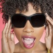 Close-up of an African American woman wearing sunglasses over colored background — Stock Photo