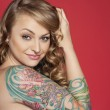 Portrait of beautiful young tattooed woman over colored background — Stock Photo #21893669