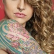 Beautiful young woman looking sideways with tattooed arm — Foto Stock