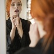 Young female applying lip liner in front of mirror — Stock Photo #21895845