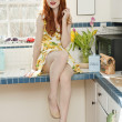 Portrait of a beautiful young woman in a dress at kitchen counter — Stock Photo