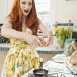 Young redheaded woman preparing omelet in kitchen — Stock Photo