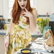 Beautiful young woman looking at omelet in frying pan — Stock Photo