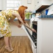 Side view of young woman opening oven door — Stock Photo
