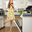 Full length of a terrified young woman looking at open oven — Stock Photo