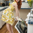 Full length portrait of a young woman standing by an open oven — Stock Photo