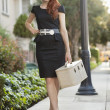 Full length of elegant womin dress walking with vanity case — Stockfoto #21896745