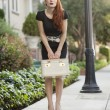 Full length of stylish womholding vanity case — Stockfoto #21896759