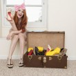 Portrait of young woman sitting near window showing high heels with suitcase full of footwear — Stock Photo