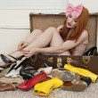 Young woman with bow headband tying footwear while sitting in suitcase — Stock Photo