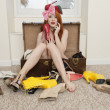 Portrait of young woman sitting in suitcase with footwear lying on floor — Stockfoto