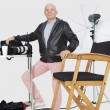Full length portrait of a happy senior photographer with equipments in studio — ストック写真