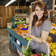 Beautiful young woman listening to mobile phone while standing with basket in market — Stockfoto
