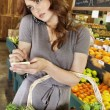 Beautiful young woman listening to mobile phone while making a note of shopping list in market — Stock Photo