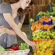 Beautiful young woman selecting fruit in market — Stock Photo