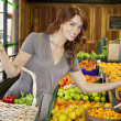 Portrait of a happy young female shopping for fruits in market — Stock Photo #21898285
