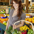Stock Photo: Portrait of beautiful brunette with basket shopping in market