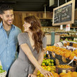 Beautiful young couple looking at each other while shopping in supermarket — Stock Photo