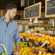 Handsome young man shopping for fruits in market — Stock Photo
