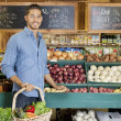 Handsome young man holding basket at vegetable stall in supermarket — Stock Photo #21898389