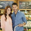 Portrait of a happy young couple in supermarket — Stock Photo