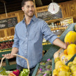 Handsome young man shopping for fruits in supermarket — Stock Photo #21898441