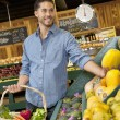 Handsome young man shopping for fruits in supermarket — Stock Photo