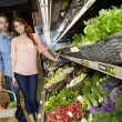 Young couple shopping for vegetables in supermarket — Stock Photo