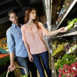 Beautiful young couple shopping together in market — Stock Photo
