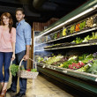 Portrait of young couple standing with vegetable basket in supermarket — ストック写真