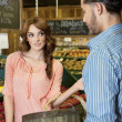 Woman looking at store clerk in supermarket — Stock Photo