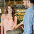 Happy young woman looking at store clerk in supermarket — Stock Photo