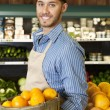 Happy salesperson with basket full of oranges in market — Stock Photo
