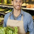 Happy young sales clerk holding bok choy in supermarket - Stock Photo