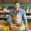 Portrait of a happy young salesman with vegetable basket in supermarket — Stock Photo #21898605
