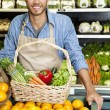 Portrait of a happy man with vegetable basket standing near oranges stall in supermarket — Stock Photo #21898611