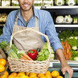 Portrait of a happy man with vegetable basket standing near oranges stall in supermarket — Stock Photo