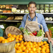 Portrait of man in supermarket with vegetable basket standing near oranges stall — Stock Photo