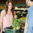 Beautiful young woman looking at store clerk in supermarket — Stock Photo